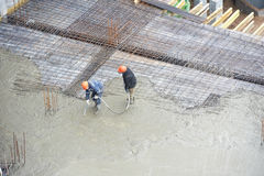 Builder workers at concrete pouring work Royalty Free Stock Photo