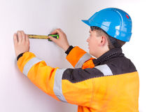 Builder in working clothes measuring wall Stock Photography