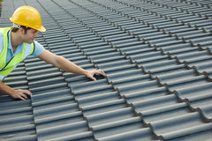 Builder Working On Roof Of New Building Stock Photos