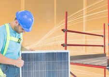 Builder working in a solar panel beside  3D scaffolding. Digital composite of builder working in a solar panel beside  3D scaffolding Stock Photo
