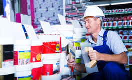 Builder workman in household store. Cheerful builder workman in uniform picking paint tin in Stock Image