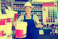 Builder workman in household store. Smiling builder workman in uniform picking paint tin in Stock Photos