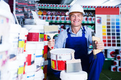Builder workman in household store. Smiling builder workman in uniform picking paint tin in Stock Photography