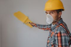 The builder works at the construction site and measures the ceiling. A worker in an orange helmet and a paint roller. Paints the wall Stock Images