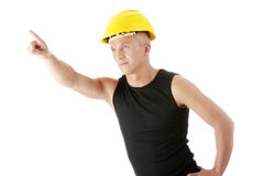 Builder in yellow helmet pointing up. Stock Photos