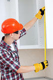 Builder with yellow tape measure Stock Photo