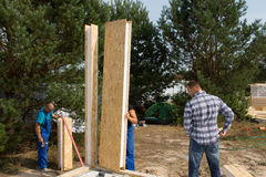 Builders aligning insulated wall panels Royalty Free Stock Photos