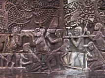 Builders of Angkor. Bas-relief at the Bayon depicting construction workers carving bricks for the temples of Angkor Royalty Free Stock Photography