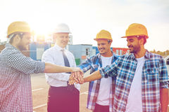 Builders and architects with hands on top. Business, building, partnership, gesture and people concept - smiling builders and architects in hardhats with hands Royalty Free Stock Photos