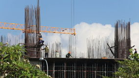 Builders assemble steel  skyscraper frame against white clouds stock footage