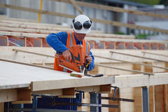 Builders bang it home. A builder uses a nail gun to secure timber on the verandah of new building Stock Image