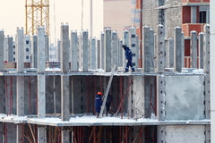 Builders in blue clothes on construction of building Stock Image