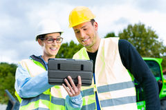 Builders with blueprint on construction site Stock Photography