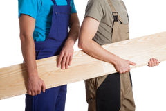 Builders with board. Two builders in overalls holding a wooden board royalty free stock photos