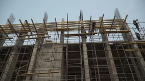 Builders building white brick wall on construction site. Clip. Panorama shot. HD stock video footage