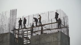 Builders building white brick wall on construction site. Clip. Panorama shot. HD stock video