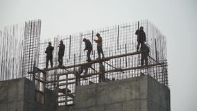 Builders building white brick wall on construction site. Clip. Panorama shot. HD stock footage