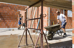 Builders carrying wheelbarrows Royalty Free Stock Image
