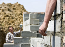 Builders checking level. Two house builders checking if the wall is even. One is holding a nail with a string attached, the other is holding another end of the stock images