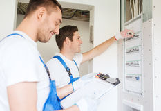 Builders with clipboard and electrical panel Royalty Free Stock Photos