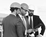 Builders at the construction site. Board of architects wear smart suits, ties and hardhats. On nature background. Constructors hold clip folder. Construction Stock Photo