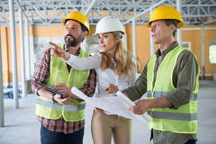 Builders and contractor talking during work on construction site Stock Photos