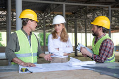 Builders and contractor talking during work on construction site Stock Photography