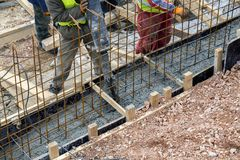 Builders crew working on concreting formwork. For the foundation under construction, purring steel rebar reinforced Royalty Free Stock Photography