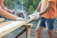 The builders cuts the board with a circular saw. The worker cuts the board equipment construction wood tool carpenter carpentry wooden machine industry blade royalty free stock image