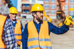 Builders discussing work while standing Royalty Free Stock Image