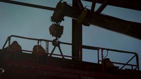 Builders are engaged in the installation of complex metal structures. The construction of a shop or skyscraper. Frame on the background of the sun and sky stock footage
