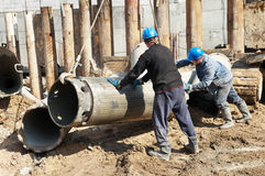 Builders with equipment for piling. Couple workers installing a tube metal form for piling with continuous concrete casting Royalty Free Stock Photography