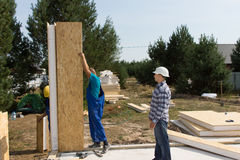 Builders erecting insulated wall panels Royalty Free Stock Photo