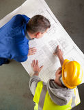 Builders examine blueprints Royalty Free Stock Photos