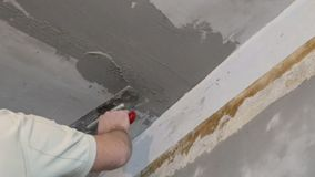 Builders float in hand applying plaster on the ceiling stock footage