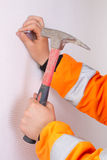 Builders hands hammering a nail. To the wall Stock Image