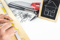 Builders hands measuring a wooden plank Royalty Free Stock Photos