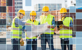 Builders in hardhats and vests with blueprint. Business, building, teamwork, technology and people concept - group of smiling builders in hardhats and highly Stock Photo