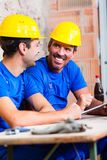 Builders having break on construction site Royalty Free Stock Photo