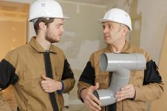 Builders holding sewer pipes. Pipe royalty free stock images