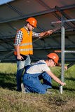 Builders installing frame with solar panels on helical pile. Engineers setting screw piles for solar power station Royalty Free Stock Image