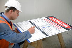 Builders look out for safety. A builder fills out the hazards board to be posted outside the construction site Stock Image