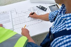 Builders Looking at Floor Plans. High angle close up of two construction workers looking at floor plans and engineering documentation on site royalty free stock photo