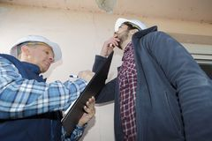 Builders looking at peeling paint on interior ceiling. Builders looking at peeling paint on an interior ceiling royalty free stock photo