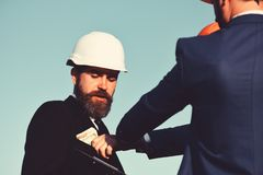 Builders make bargain. Architects with confused face in formal wear. And white helmet looks at money. Workers put cash into engineers pocket on blue sky stock photography