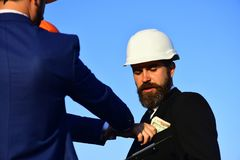 Builders make bargain. Architects with confused face in formal wear. And white helmet looks at money. Workers put cash into engineers pocket on blue sky stock photos