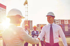 Builders making handshake on construction site Stock Images