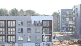 Builders men paint newly build modern house walls in white. 4K. VILNIUS, LITHUANIA - MARCH 18, 2015: Builders men in crane lift paint newly build modern house stock footage
