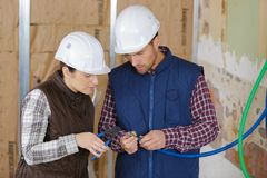 Builders people in uniform cutting cables. Woman royalty free stock photography