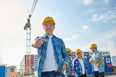 Builders pointing finger at you on construction. Business, building, teamwork and people concept - group of smiling builders in hardhats pointing finger at you royalty free stock photo